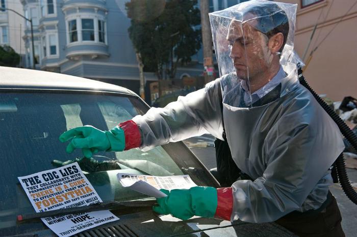 Photographie de Jude Law tirée du film Contagion réalisé par Steven Soderbergh. Nous y voyons le personnage incarné par Jude Law déposer un flyer d'alerte sur une voiture. Il est en tenue spéciale afin d'éviter toute contamination et contact avec l'air extérieur.