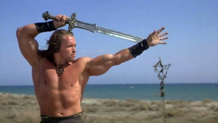 Photographie d'Arnold Schwarzenegger dans le film Conan le barbare de John Milius. Sur la photo, le guerrier s'entraîne à manier l'épée.