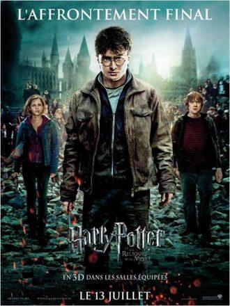 Affiche du film Harry Potter et les reliques de la mort partie 2 sur laquelle le trio de héros sont face à l'objectif devant l'école de Poudlard dévastée.