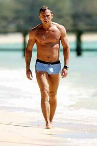 Photo de Daniel Craig avançant sur la plage en maillot de bain.
