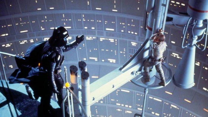 Photo de Luke Skywalker et Dark Vador dans le film L'Empire contre-attaque. Luke est sur le point de tomber dans le vide alors que Vador tente de le persuader de rejoindre le côté obscur.