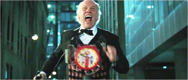 Photo de John Malkovich courant vers l'objectif, habillé de bâtons de dynamite, dans le film RED.
