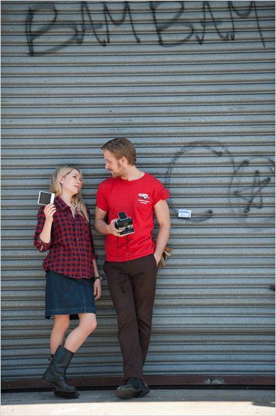 Photo de Michelle Williams et Ryan Gosling discutant ensemble devant un rideau en fer dans la rue dans le film Blue Valentine de Derek Cianfrance.