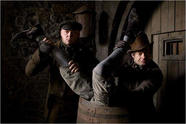 Photo de Simon Pegg et Andy Serkis mettant un cadavre dans un tonneau dans le film Cadavres à la pelle.