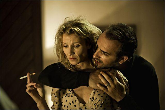 Photo tirée du film Les Infidèles sur laquelle Jean Dujardin et Alexandra Lamy s'étreignent avec un air triste.