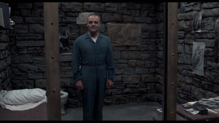 Photo d'Anthony Hopkins se tenant debout dans sa cellule dans le film Le silence des agneaux de Jonathan Demme.