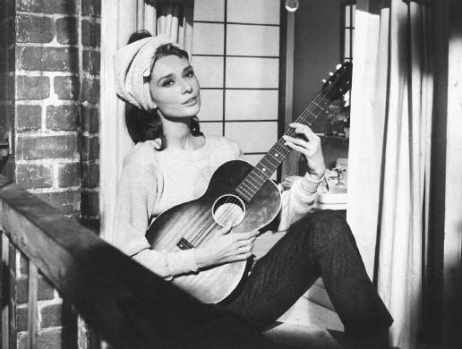 Photo d'Audrey Hepburn jouant de la guitare et chantant Moon River dans le film Diamants sur canapé de Blake Edwards.