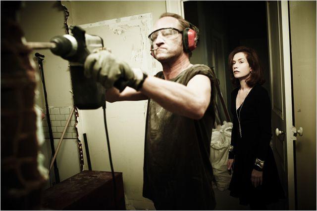 Photo de Benoit Poelvoorde et Isabelle Huppert dans le film Mon pire cauchemar. Poelvoorde bricole alors qu'Huppert l'observe.