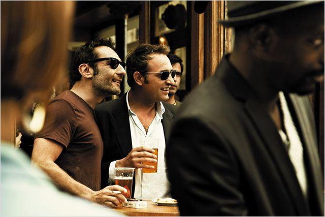 Photo de Gilles Lellouche et Jean Dujardin prenant un verre à l'extérieur d'un bar dans les film Les Infidèles.