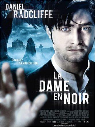 Affiche de La dame en noir sur laquelle Daniel Radcliffe met sa main face à l'objectif. Une dame en noir marche dans un paysage sombre au second plan.