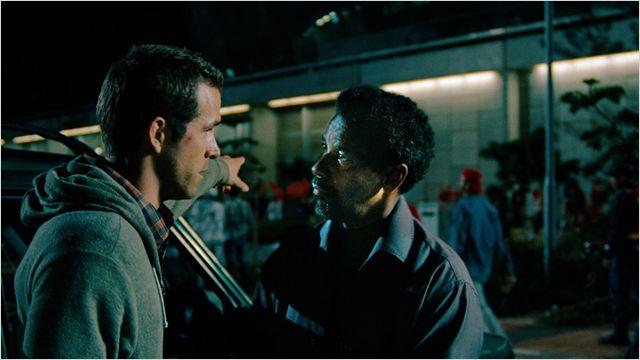 Photo de Ryan Reynolds et Denzel Washington discutant dans une rue dans le film Sécurité Rapprochée.