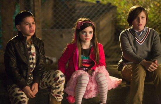 Photo des trois enfants assis dans un jardin que Jonah Hill doit garder dans le film The Sitter.