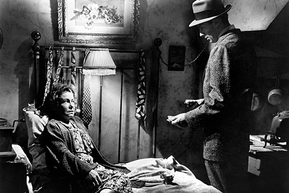 Photo de Thelma Ritter assise dans son lit et questionnée par un autre personnage dans le film Le port de la drogue de Samuel Fuller.