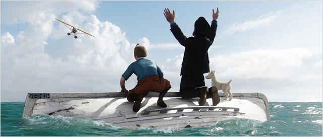 Photo de Tintin et du Capitaine Haddock de dos sur une barque qui sombre et faisant des signes à un avion dans le film Les aventures de Tintin : Le secret de la Licorne réalisé par Steven Spielberg.