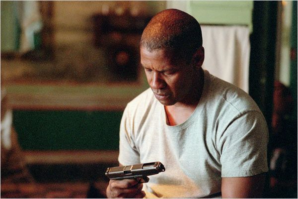 Photo de Denzel Washington observant une arme qu'il tient avec désespoir dans le film Man On Fire de Tony Scott.