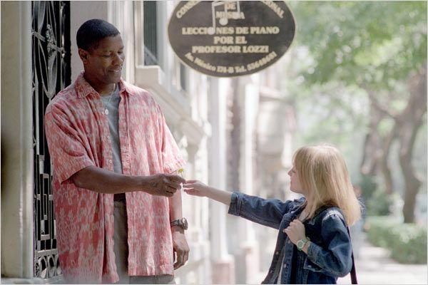 Photo tirée du film Man On Fire de Tony Scott sur laquelle Dakota Fanning tend une fleur à Denzel Washington dans une rue.