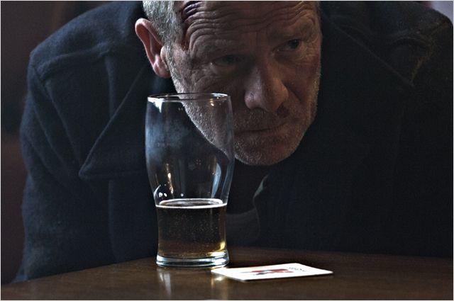 Photo de Peter Mullan dans le film Tyrannosaur. L'acteur a du sang sur le visage, est assis à la table d'un pub avec une bière et est penché comme s'il observait attentivement quelqu'un.