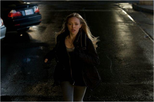 Photo d'Amanda Seyfried dans le film Disparue qui court dans une rue au milieu de la route en pleine nuit.