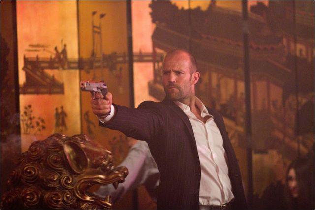 Photo de Jason Statham braquant une arme sur ses ennemis dans le film Safe.