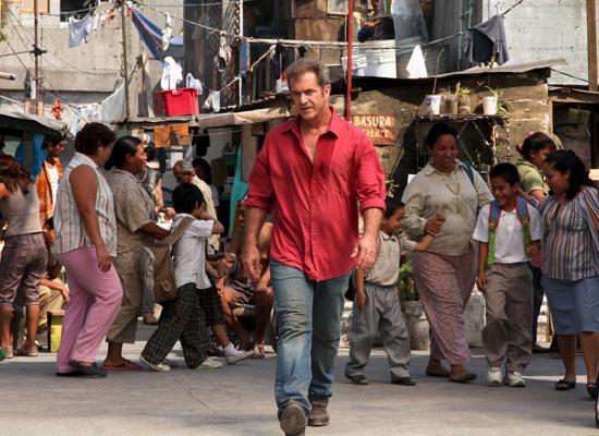 Photo de Mel Gibson dans le film Get The Gringo qui avance déterminé face à l'objectif dans une rue mexicaine.