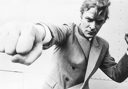 Photo de Michael Caine pris de face et mettant un coup de poing dans l'objectif.