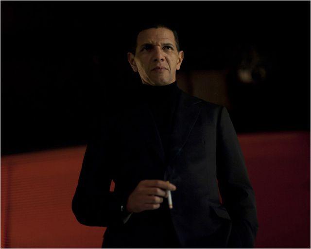 Photo de Roschdy Zem dans le film Une Nuit de Philippe Lefebvre. Le comédien fume une cigarette dans une boîte de nuit.