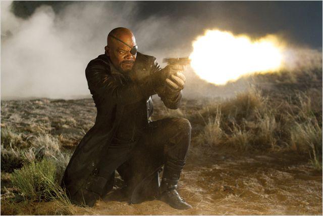 Photo de Samuel L. Jackson dans le film Avengers de Joss Whedon. L'acteur est dans le désert, appuyé sur une jambe et tire au pistolet.