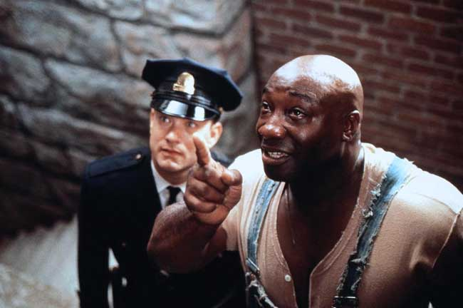 Photo de Tom Hanks et Michael Clarke Duncan dans le film La Ligne Verte de Frank Darabont. Michael Clarke Duncan montre quelque chose en l'air à Tom Hanks dans la prison.