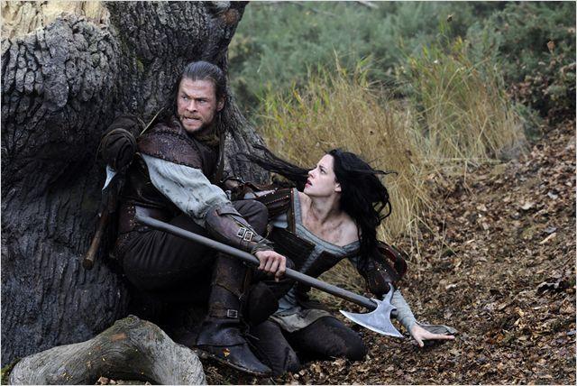 Photo de Chris Hemsworth et Kristen Stewart dans le film Blanche Neige et le Chasseur. Le Chasseur protège Blanche-Neige en la cachant derrière un arbre.