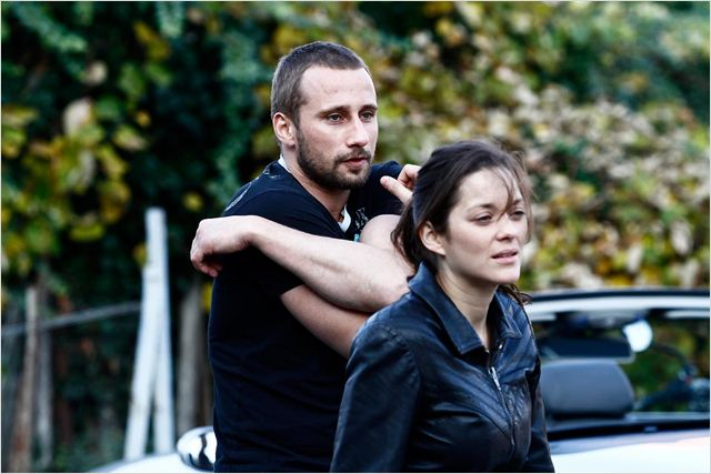 Photo de Matthias Schoenaerts et Marion Cotillard dans le film De Rouille et d'Os de Jacques Audiard ensemble avec un combat de rue pour lequel Schoenaerts se prépare.