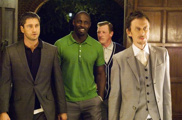Photo de la Horde Sauvage composée notamment de Gerard Butler et Idris Elba pénétrant dans une soirée dans le film Rocknrolla de Guy Ritchie.