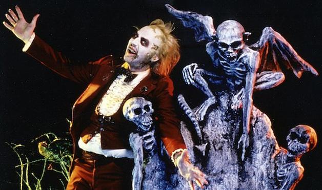 Photo de Michael Keaton dans le film Beetlejuice de Tim Burton. L'acteur incarne le rôle titre et fanfaronne dans un cimetière.