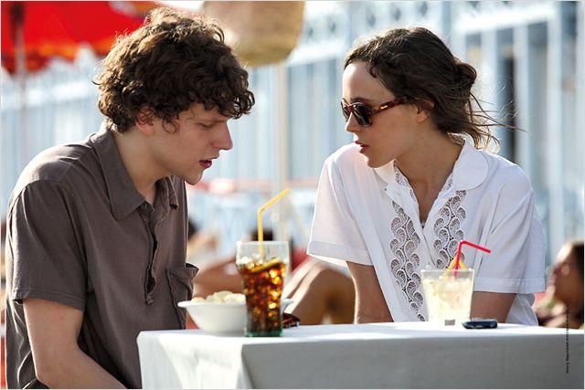 Photo de Jesse Eisenberg et Ellen Page dans le film To Rome with Love de Woody Allen. Les deux discutent ensemble à la terrasse d'un café.