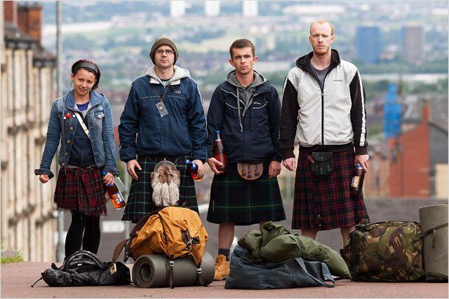 Photo des quatre personnages principaux de La Part des Anges de Ken Loach posant devant l'objectif en kilt et avec leurs bagages.