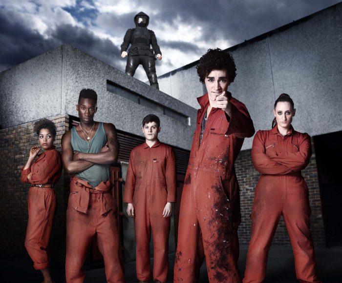 Photo de la saison 2 de la série Misfits où la bande est face à l'objectif dans leur tenue de TIG. Un mystérieux individu masqué se tient au dessus d'eux.