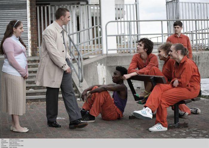 Photo de la série Misfits sur laquelle les cinq héros discutent avec des ennemis élégamment vêtus.