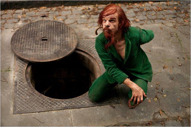 Photo du personnage Monsieur Merde du film Holy Motors de Leos Carax, interprété par Denis Lavant. Monsieur Merde s'apprête à pénétrer dans une bouche d'égout.