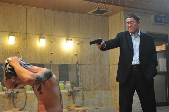 Photo de Takeshi Kitano dans Outrage qui s'apprête à éliminer un yakuza dans une salle de bains.