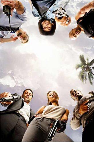 Photo du film The Losers sur laquelle l'équipe de mercenaires est regroupée et prise en contre-plongée.