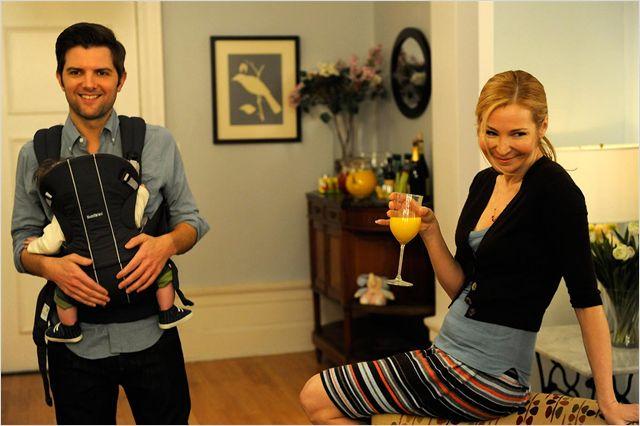 Photo d'Adam Scott et Jennifer Westfeldt dans le film Friends with kids. Dans un appartement, les deux acteurs rient avec des amis. Scott porte un bébé alors que Westfeldt boit un verre.