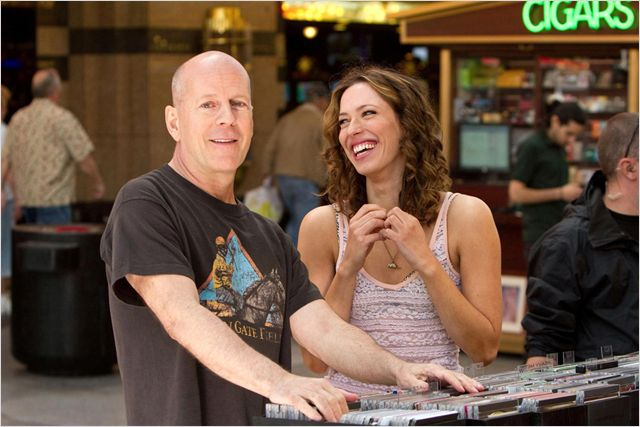 Photo de Bruce Williset Rebecca Hall dans le film Lady Vegas de Stephen Frears. Les deux acteurs sont chez un disquaire et rient ensemble.