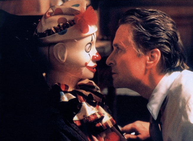 Photo de Michael Douglas contemplant étrangement un clown dans le film The Game de David Fincher.