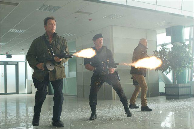 Photo d'Arnold Schwarzenegger, Bruce Willis et Sylvester Stallone tirant sur des ennemis côte à côte dans Expendables 2 de Simon West.