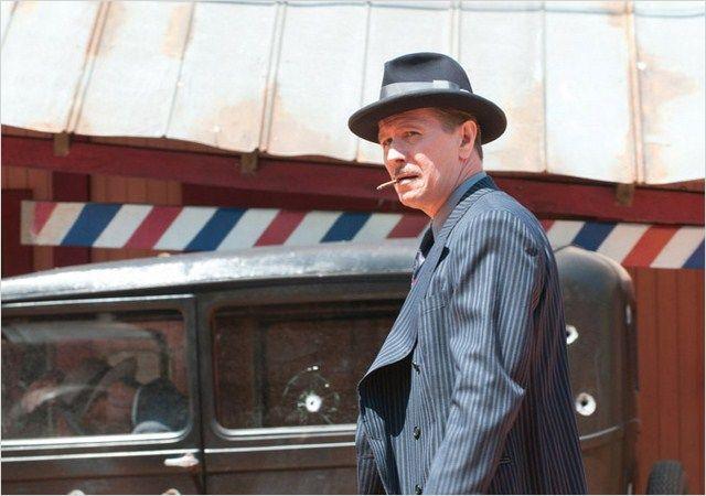 Photo de Gary Oldman dans le film Des Hommes sans Loi de John Hillcoat. L'acteur est dans une rue devant une voiture criblée de balles, regarde à l'horizon, une cigarette à la bouche.