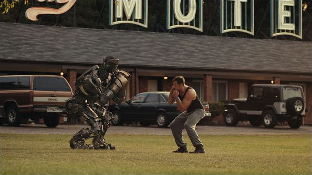 Photo de Hugh Jackman dans le film Real Steel s'entraînant à la boxe sur le parking d'un motel avec un robot.