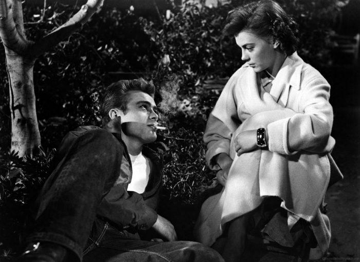Photographie de James Dean et Natalie Wood dans le film La fureur de vivre de Nicholas Ray. Les deux sont assis dans un bois et cherchent à se charmer.