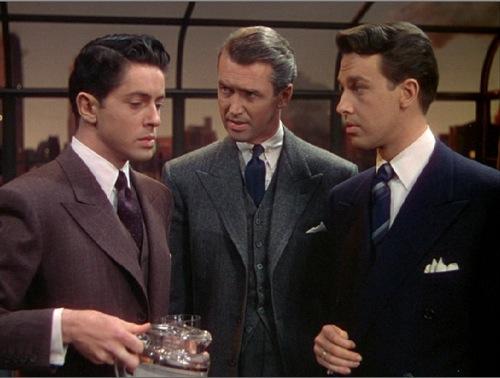 Photo de James Stewart dans le film La Corde d'Alfred Hitchcock. Dans un appartement, Stewart se trouve entre les deux meurtriers du film et mène son enquête en leur posant des questions.