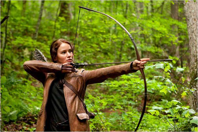 Photo de Jennifer Lawrence dans le premier volet de la saga Hunger Games réalisé par Gary Ross. L'actrice est dans le bois et s'apprête à tirer à l'arc.