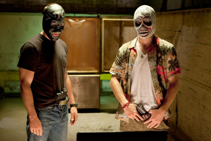 Photo de Taylor Kitsch et Aaron Johnson dans le film Savages d'Oliver Stone. Armés et portant des masques de catcheurs mexicains, les deux acteurs semblent parler à une autre personne à travers la webcam d'un ordinateur.