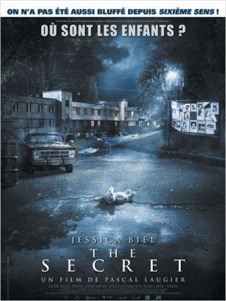 Affiche du film The Secret de Pascal Laugier. Au milieu d'un village délabré et sous la pluie, un ours en peluche est sur le sol comme s'il était abandonné.